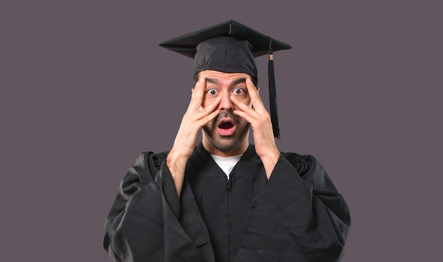 Man on his graduation day university surprised and covering face with hands