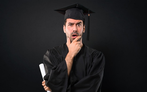 Man on his graduation day university surprised and shocked while looking right