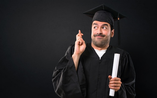 Man on his graduation day university with fingers crossing and wishing the best. making a