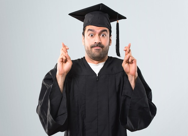 Man on his graduation day university with fingers crossing and wishing the best