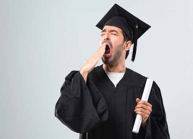 Man on his graduation day university yawning and covering wide open mouth with hand