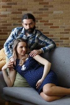 A man and his pregnant wife are posing on a sofa at home