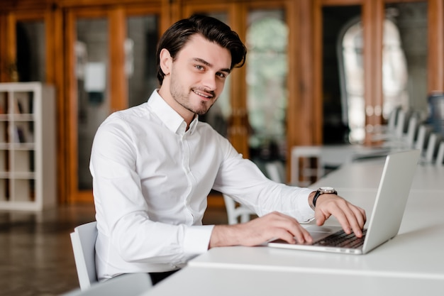 Man at his workplace with laptop in the office
