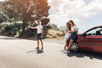 Man hitchhiking on road and her friends looking at map