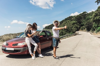 Man hitchhiking on road standing in front of female friends looking at map