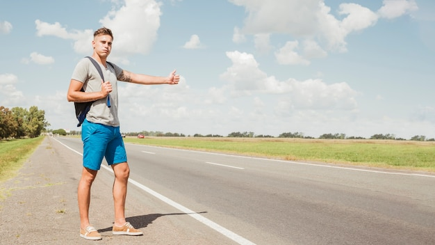 Man hitchhiking on a road