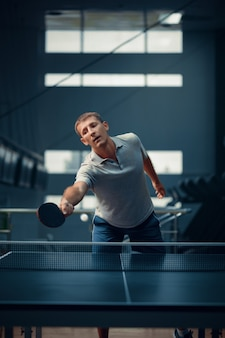Man hits the ball at the net, table tennis, ping pong player