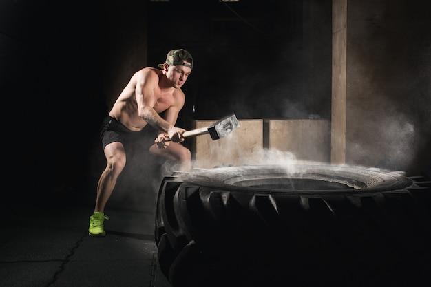 Человек бьет по шинам. тренировка в тренажерном зале с молотком и тракторной шиной