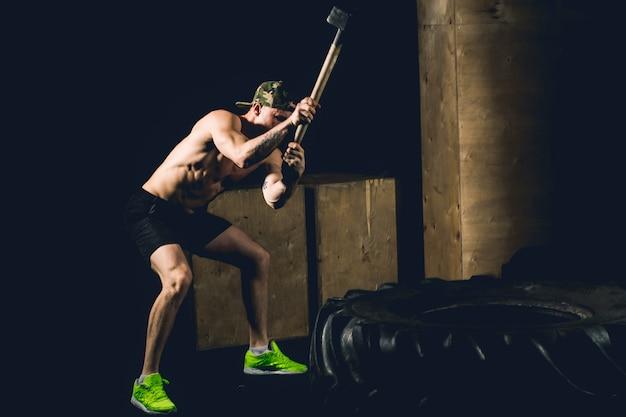 남자는 타이어를 친다. 망치와 트랙터 타이어 체육관에서 운동