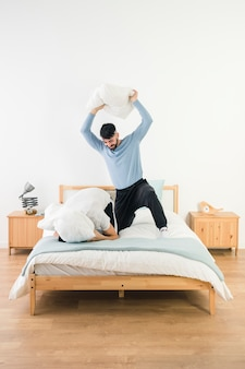 Man hitting his boyfriend with white pillow on bed