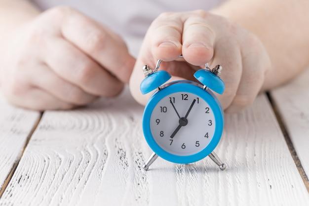 Человек держится и шокирован поздним будильником