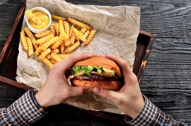男はハンバーガーを手に持っています。ハンバーガーとフライドポテトでお食事。