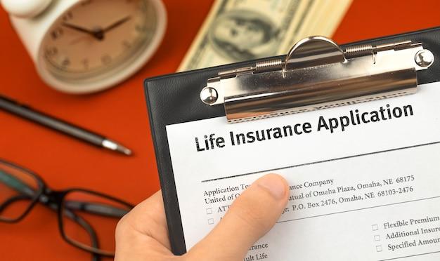 남자는 생명 보험 신청서와 양식이 있는 클립보드를 손에 들고 있습니다. 돈, 알람 시계, 펜이 있는 사무실 책상 배경