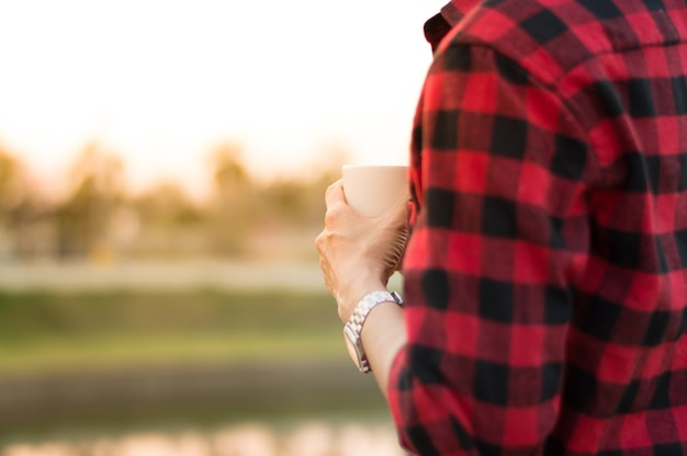 Man hold coffee cup in hand stand alone near the lake with morning light.