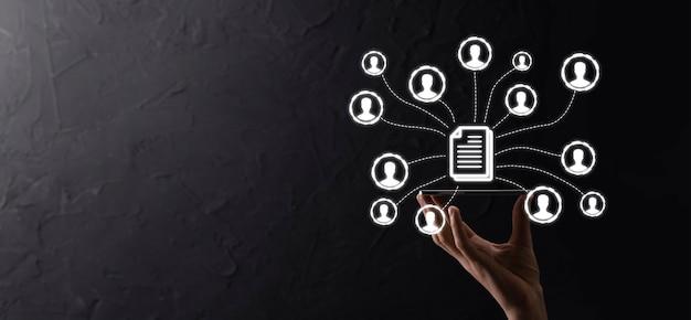 Человек держать документ и значок пользователя. корпоративная система управления данными dms и концепция системы управления документами. бизнесмен нажимает или публикует документ, связанный с корпоративными пользователями.