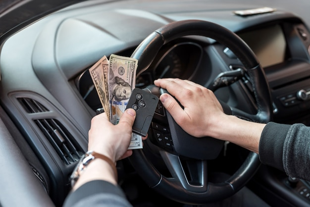 Man hold dollar and car key for pay rent or bribe