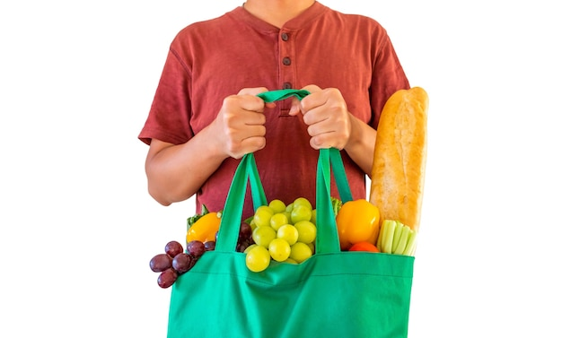 Man hold eco friendly green reusable shopping bag filled with full fresh fruits and vegetables grocery product isolated