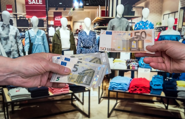 Man hold euro bills in clothes shop. purchase concept