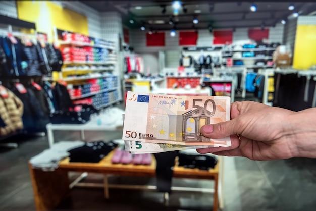 男は洋服店でユーロ紙幣を持っています。購入コンセプト
