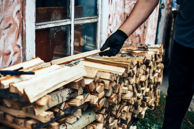 남자 장작을 잡고, 그는 나무 woodpile의 스택에 절단 나무를 넣습니다