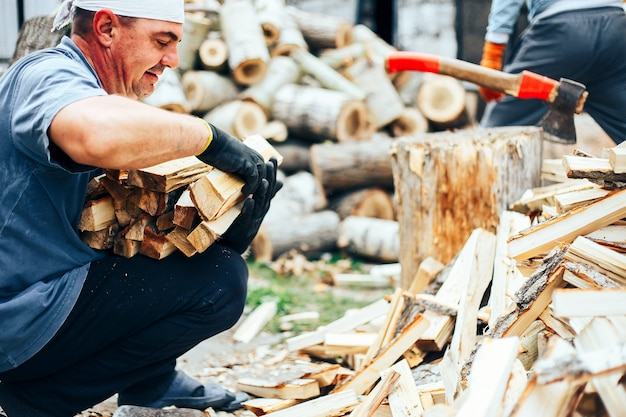 Man hold firewood, he puts cutting wood into stack of wood woodpile