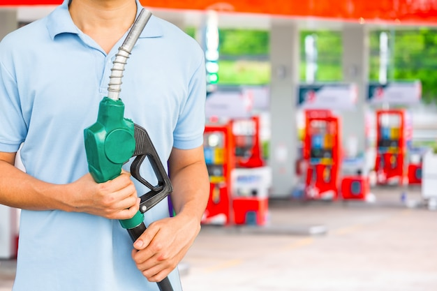 Man hold fuel nozzle to add fuel in car at gas station.
