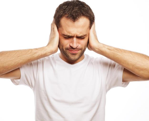 男はこめかみの耳に手をつないで、ストレスを感じる男、頭痛、落ち込み、痛み、目を閉じて白で隔離される白いtシャツを着る。
