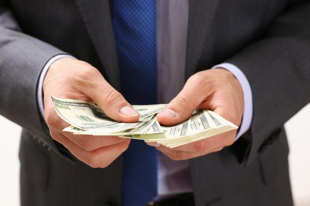 Мужчина держит в руке пачку стодолларовых купюр