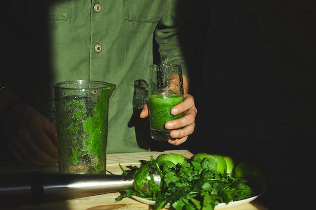 健康的なデトックススムージー、ブレンダーで調理を手にガラスを握る男