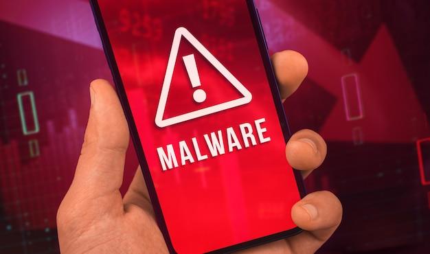 맬웨어 경고 화면이 있는 휴대전화를 들고 있는 남자, 세계 사이버 범죄의 개념 사진