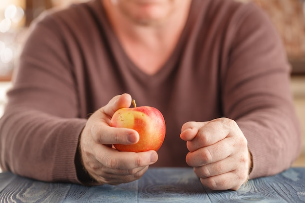 Мужчина держит одно яблоко в руке