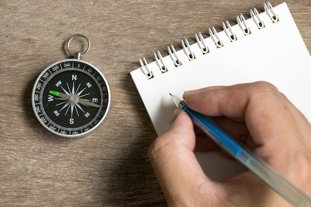 Man hold the pen to write on blank note book with compass on wood desk background