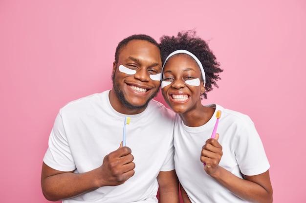 남자는 칫솔을 들고 분홍색으로 격리된 캐주얼한 흰색 기본 티셔츠를 입은 눈 아래 미용 패치를 적용합니다.