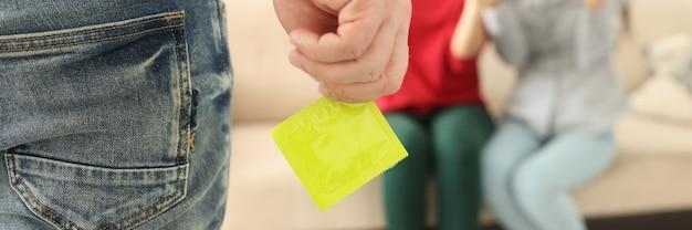 男は手に黄色のコンドームをクローズアップします。