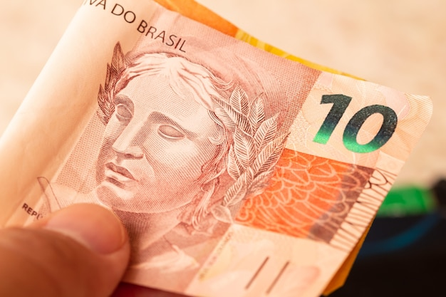 A man holding a 10 reais brazilian real banknote in closeup photography