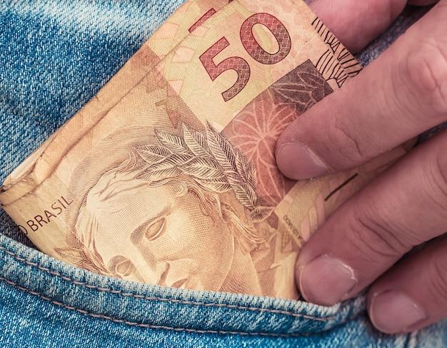 Man holding 50 reais brazilian real bills inside a pants pocket in macro photography