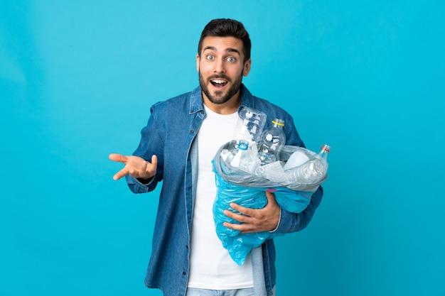 Мужчина держит мешок, полный пластиковых бутылок для переработки