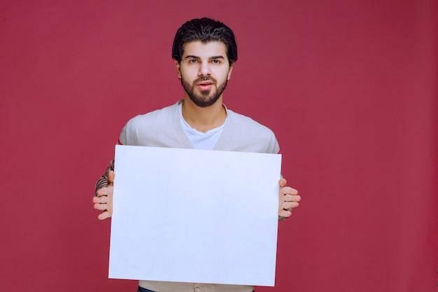 空白のアイデアボードを保持し、プレゼンテーションを行う男。