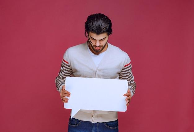 空白のアイデアボードを保持し、プレゼンテーションを行う男。 無料写真