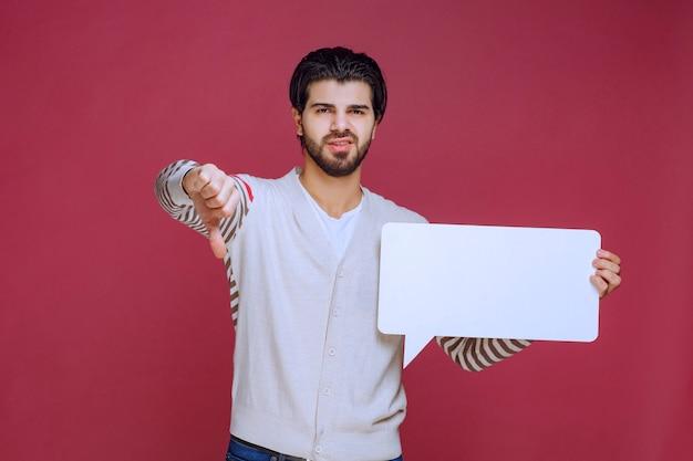 空白のアイデアボードを持って親指を下に向ける男。
