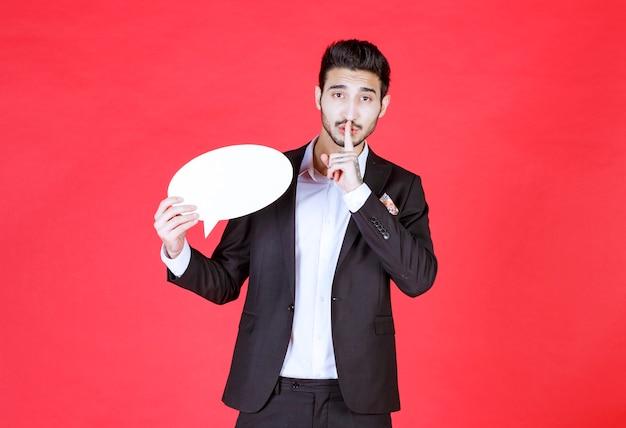 空白の楕円形の情報ボードを保持し、沈黙を求めている男。