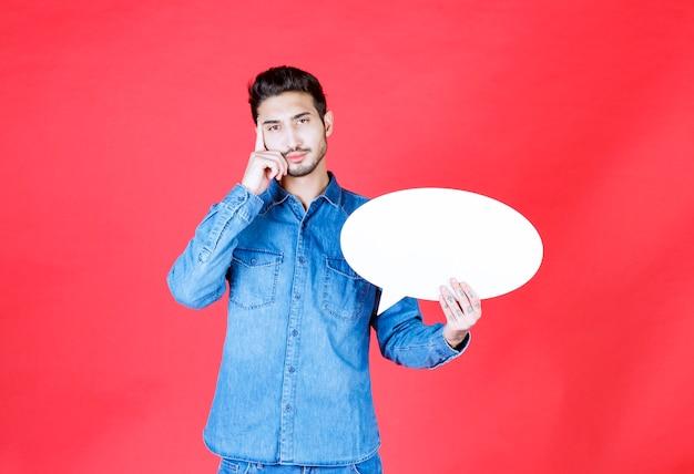 空白の楕円形の情報ボードを保持し、混乱して思慮深く見える男。