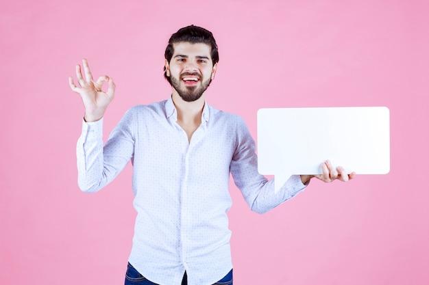 それのような空白の長方形のthinkboardを持っている男。