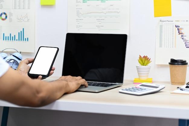 Мужчина держит смартфон с пустым экраном и использует ноутбук, калькулятор и кружку кофе с канцелярскими принадлежностями на столе, графики данных на стене офиса.