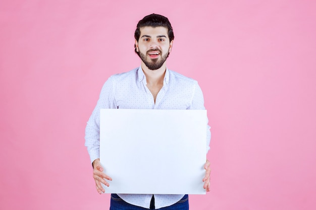 Мужчина держит перед собой пустую квадратную доску.