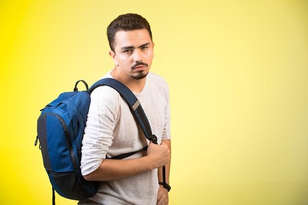 Мужчина держит синий рюкзак и смотрит прямо.
