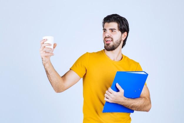 青いフォルダーとコーヒーカップを持っている男。