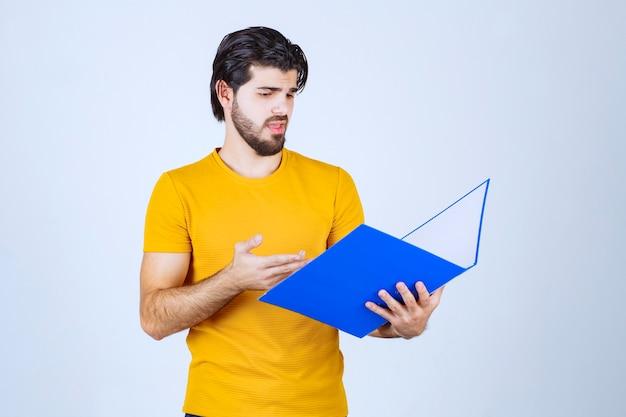 青いフォルダーを持ってレポートをチェックしている男。