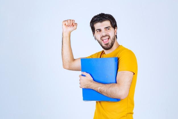 青いフォルダーを持って拳を見せている男。
