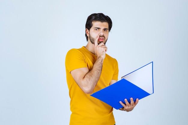 青いフォルダーを持って考えている男。